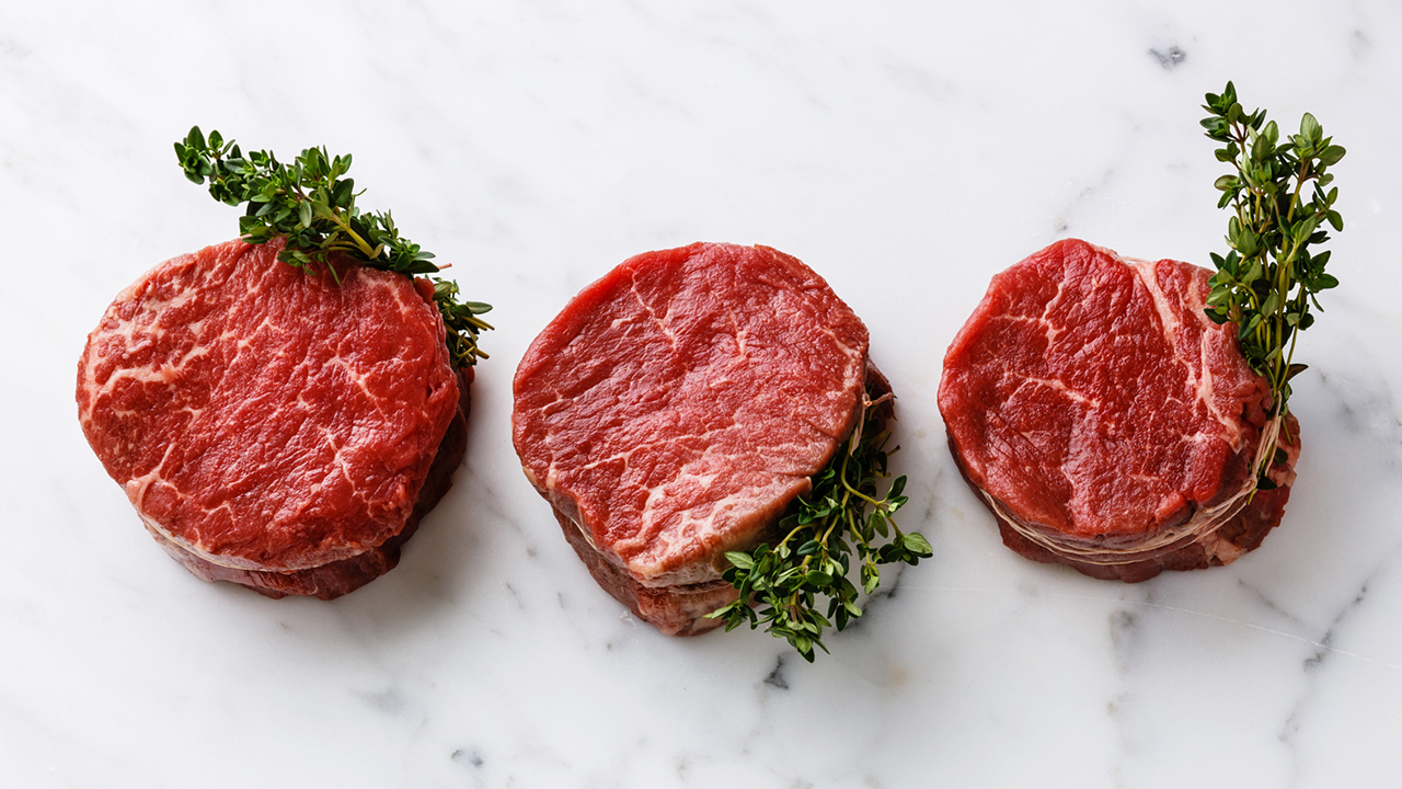 Raw fresh marbled meat Steak filet mignon and thyme on white mar